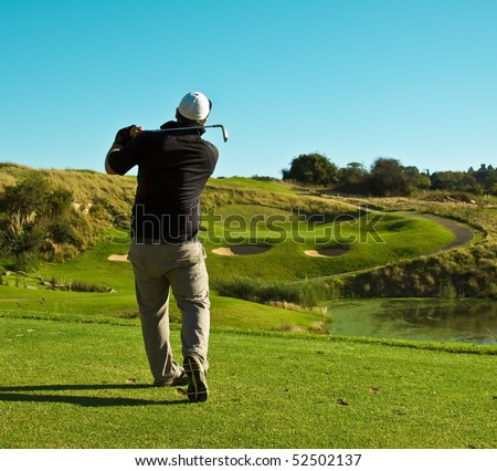 Golfer (player) standing on tee facing a green playing golf hitting a ball to the hole - stock photo