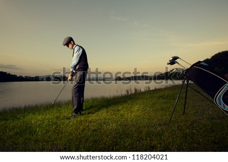 golfer playing at sunset - stock photo