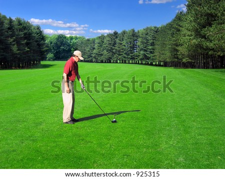Golfer prepares a fairway shot on a well-manicured course - stock photo
