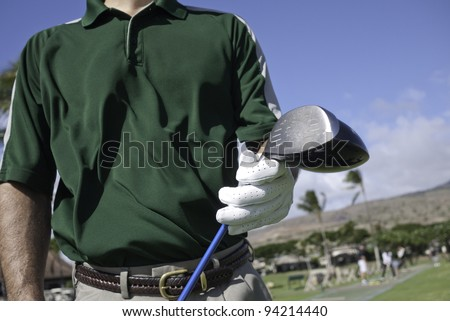 Golfer pulls out a driver club at a driving range. - stock photo