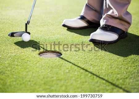 Golfer putting ball on the green on a sunny day at the golf course - stock photo