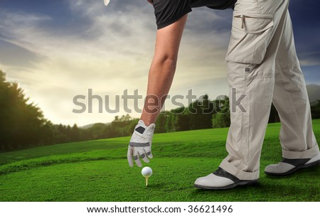 golfer putting golf ball on a tee and a beautiful natural landscape on the background - stock photo