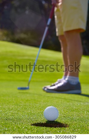 Golfer putting golf ball to hole - stock photo