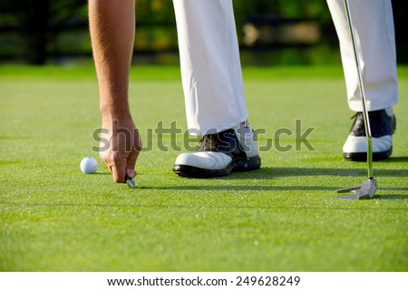 Golfer repaired green with pitch fork - stock photo