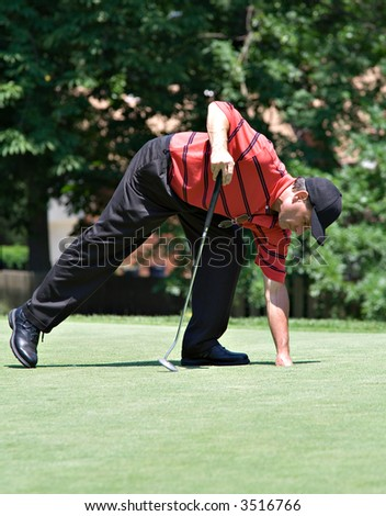 Golfer retrieving ball from hole on green. - stock photo