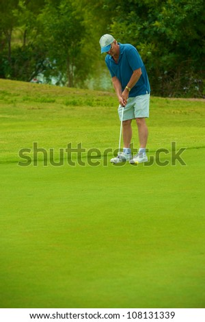 Golfer setting up for the shot with perfect form. - stock photo