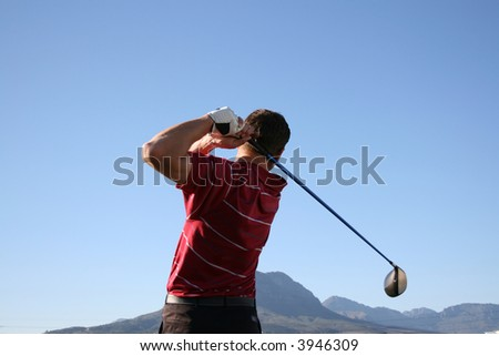 Golfer shot with a driver against blue sky Follow Through of a young professional golfer whilst practising on the range - stock photo