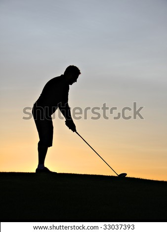 Golfer silhouette at sunrise. - stock photo