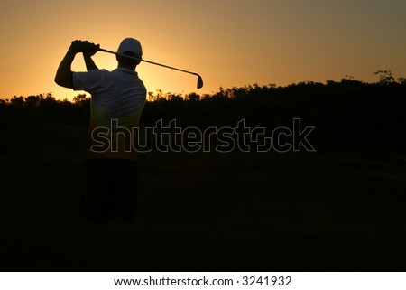 Golfer silhouette on golden sunset with black copy space - stock photo