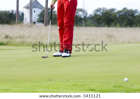Golfer standing on a green and the ball in the foreground