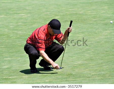 Golfer stoops down to repair the ball mark in the putting green with a golf tee. - stock photo