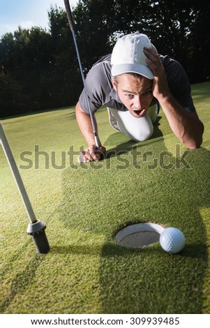 Golfer stunned because he missed his last swing Handsome golfer lying down on the green, hands on the ground Wide angle view with a beautiful forest in the background - stock photo