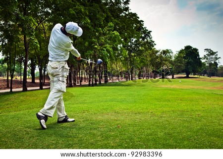 Golfer swinging his golf club and hit the golf ball from tee along the pretty green fairway on beautiful golf course - stock photo