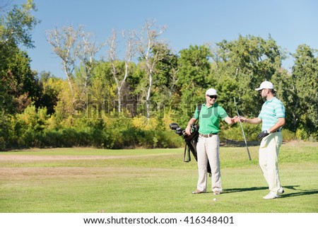 Golfer takes an iron golf club from caddy - stock photo