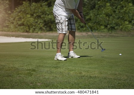 Golfer taking a shot on the green, swinging his golf club