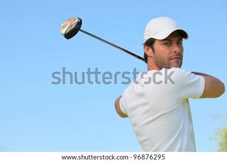 Golfer taking a swing - stock photo