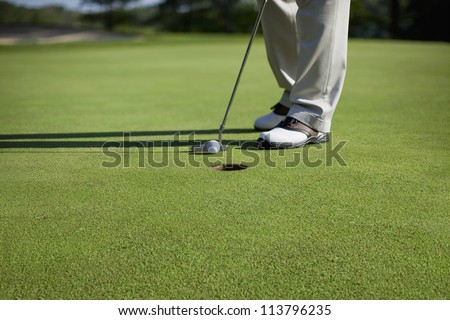 Golfer taps in a putt on a green - stock photo