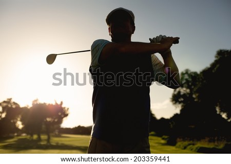 Golfer teeing off for the day on a sunny morning at the golf course - stock photo