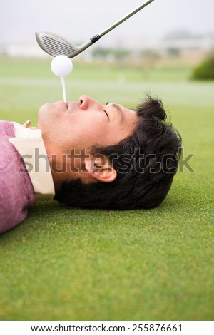 Golfer teeing off from lying man mouth at golf course - stock photo