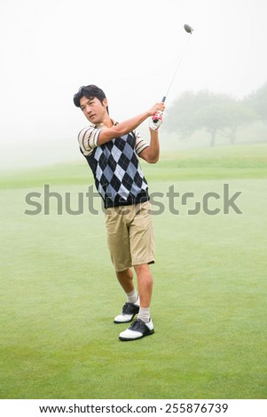 Golfer teeing off the golf course - stock photo