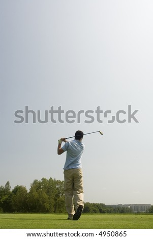 Golfer tees off - stock photo