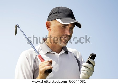 Golfer using mobile phone - stock photo