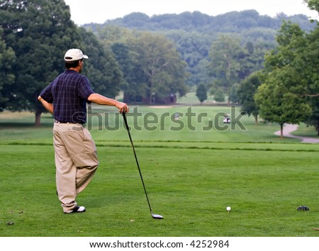 Golfer waiting for the fairway to clear so that he can make his drive from the tee box.