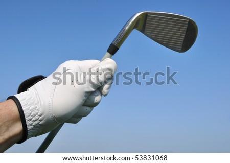 Golfer Wearing a Golf Glove Holding an Iron (Golf Club) - stock photo