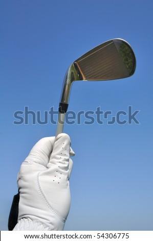 Golfer Wearing a Golf Glove Holding an Iron (Golf Club) Against a Blue Sky - stock photo