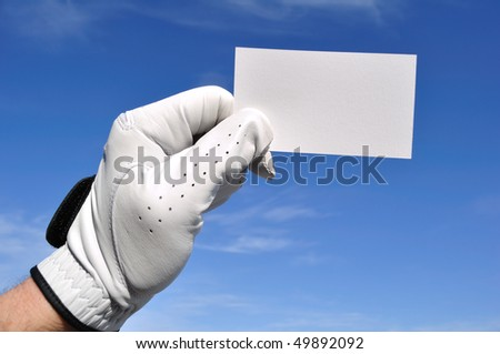 Golfer Wearing Golf Glove Holding a Blank Business Card Against a Blue Sky - stock photo