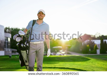 Golfer with club on a lawn - stock photo