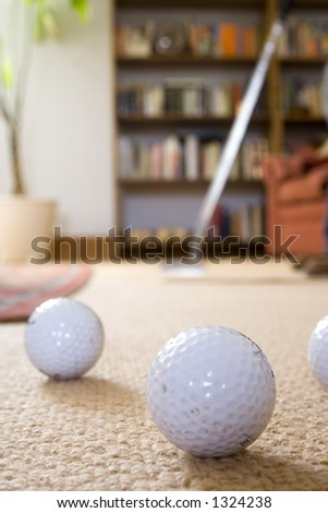 Golfer with putter rehearsing club strokes in the front room. - stock photo