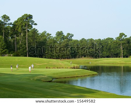 Golfers enjoying a fine day on this beautiful Myrtle Beach golf course in South Carolina. - stock photo