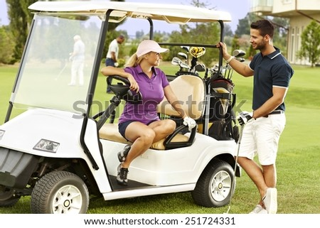 Golfers flirting in the fairway in golf cart, smiling. - stock photo
