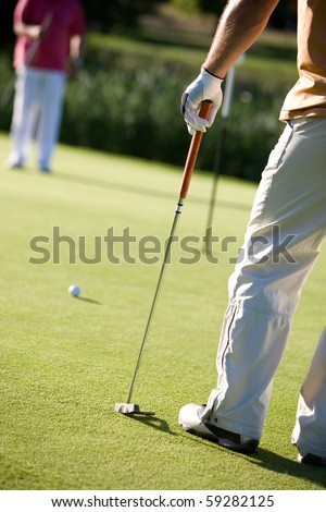 golfers playing golf on beautiful sunny day - stock photo
