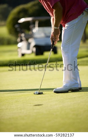 golfers playing golf on beautiful sunny day - stock photo