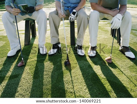 Golfers sitting on bench - stock photo