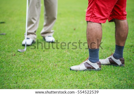 Golfers stand talking together on the golf course.