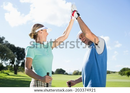 Golfing couple high fiving on the golf course on a sunny day at the golf course - stock photo
