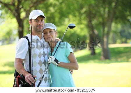 Golfing couple hugging on a course - stock photo