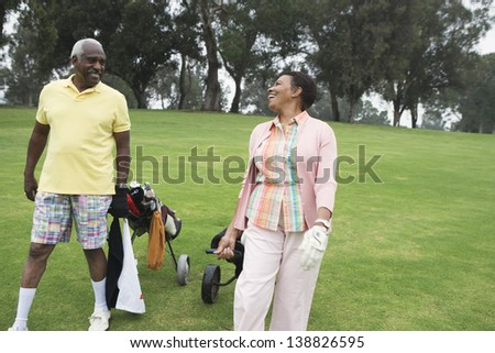 Golfing couple laughing together - stock photo