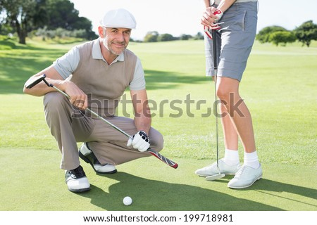 Golfing couple on the putting green with man smiling at camera on a sunny day at the golf course