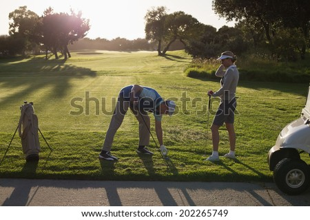 Golfing couple teeing off for the day on a sunny morning at the golf course - stock photo