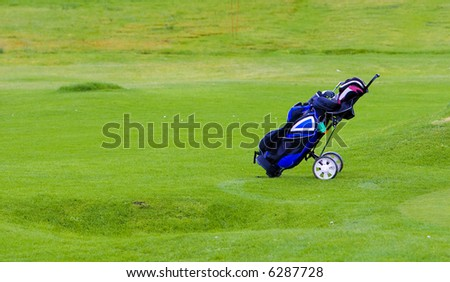 Golfing equipment in the bag over the grass. Shallow depth of field - stock photo