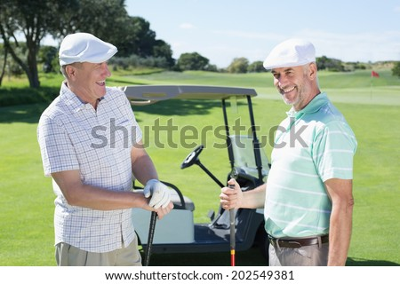 Golfing friends chatting beside their buggy on a sunny day at the golf course - stock photo