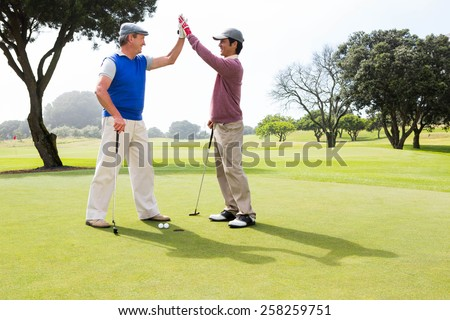 Golfing friends high fiving on the hole at the golf course - stock photo