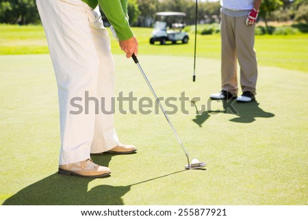 Golfing friends teeing off at the golf course - stock photo