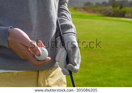 golfing man holding golf ball and club outdoors - stock photo