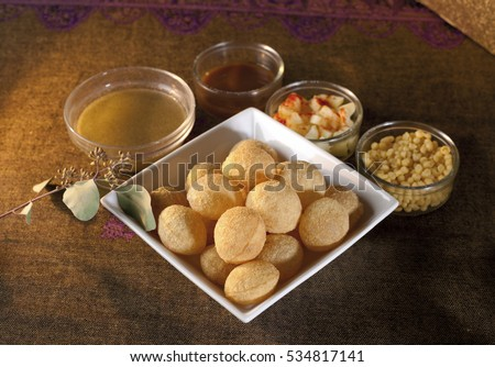 Golgappa or pani puri, an Indian snack or chat item with accompaniments in background