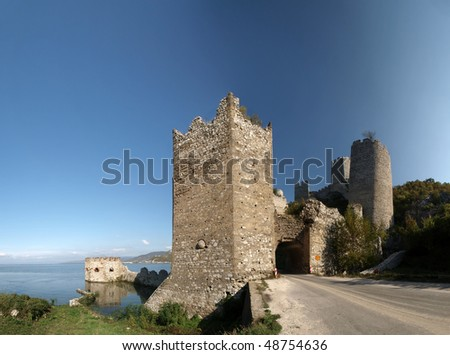 Golubac Fortress  panorama.  12th century castle located at the entrance of river Danube IRON GATE gorge. Main tower gate with fortified river dock on the left and rest of the towers on the right - stock photo